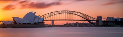 Beautiful shot of the Sydney harbor bridge with a light pink and blue sky in background at sunset